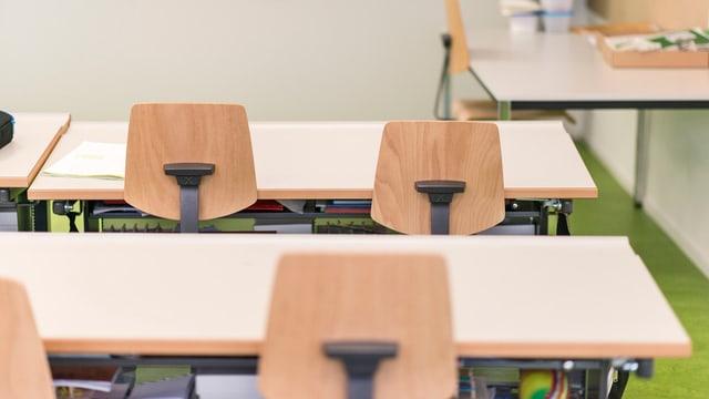 Leere Tische und Stühle in einem Schulzimmer.