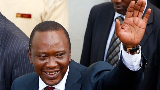 Kenyatta, im Anzug, hält eine Hand zu Gruss hoch.
