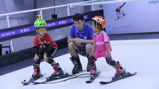 Zwei chinesische Kinder lernen Skifahren