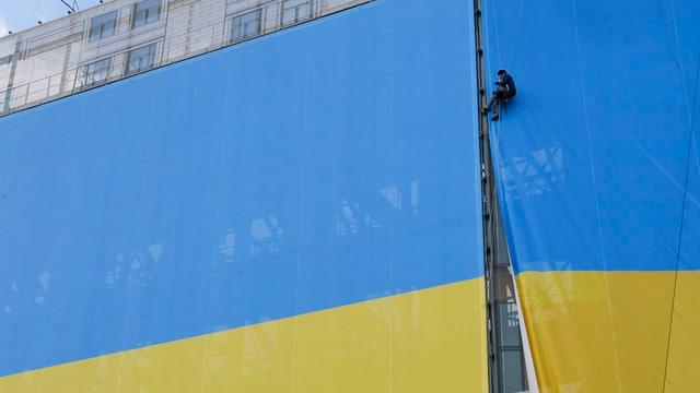 Eine Person hängt eine riesige Ukraine-Flagge an eine Wand.