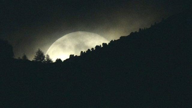 Der Vollmond geht hinter einem Berg auf.