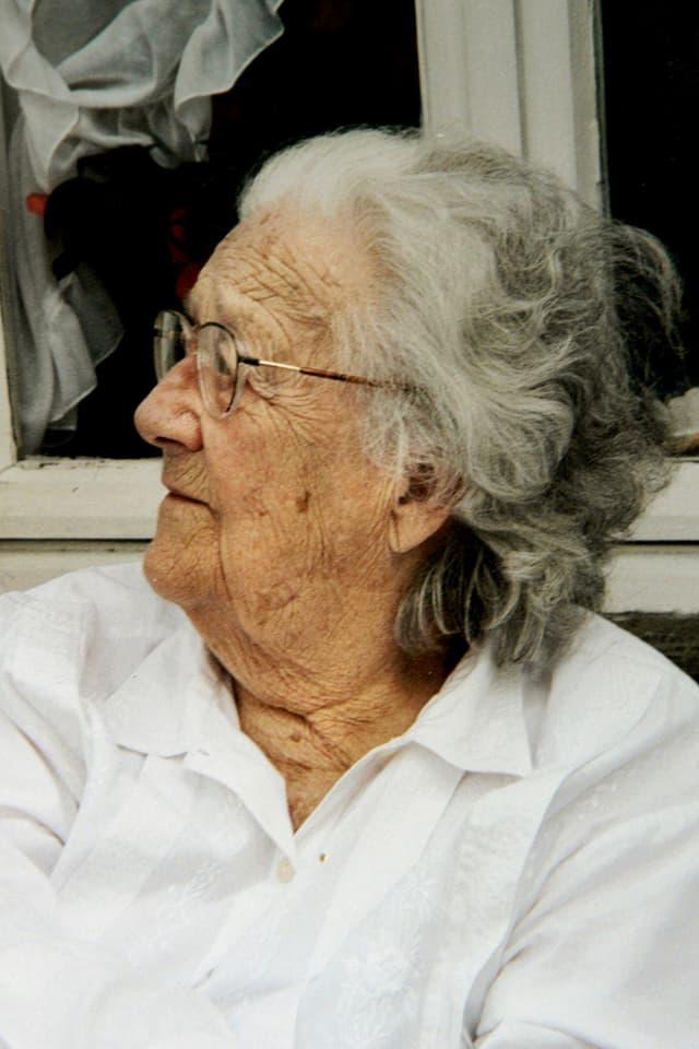 Eine ältere Frau mit Brille, zur Seite blickend.