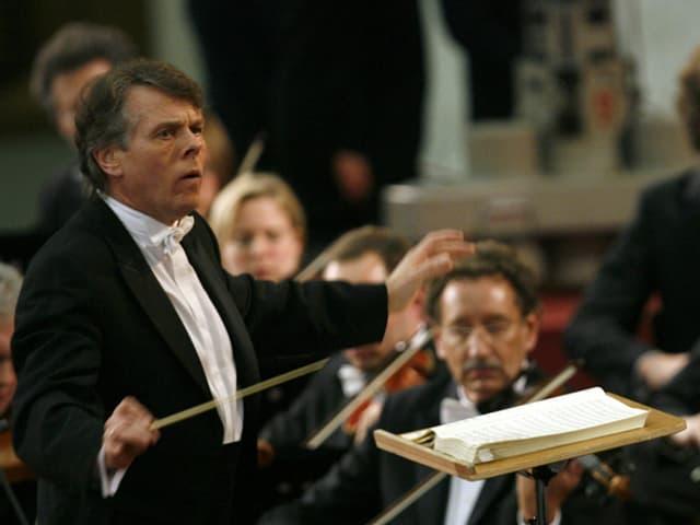 Der Dirigent mit Stock am Pult.