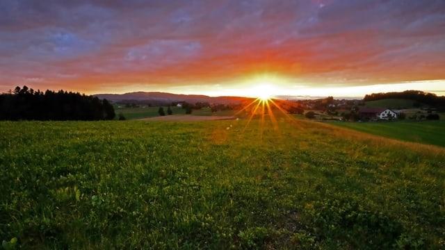 Die untergehende Sonne verfärbt die Wolken am Himmel rötlich.