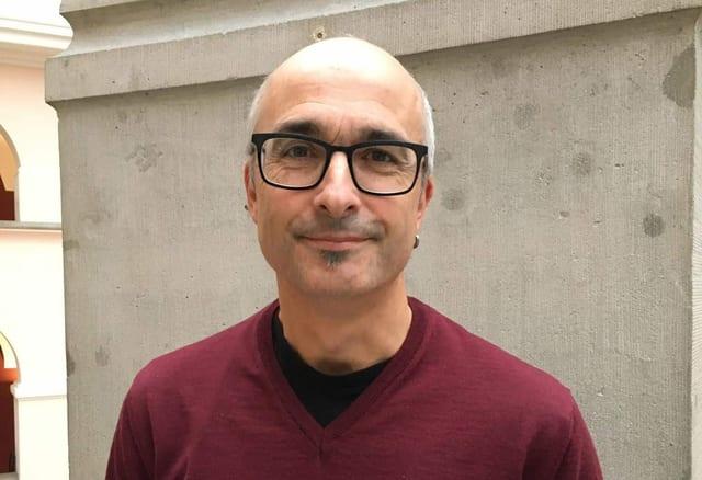 Ein Mann mit Brille steht vor einer Säule und lächelt mit geschlossenem Mund in die Kamera.