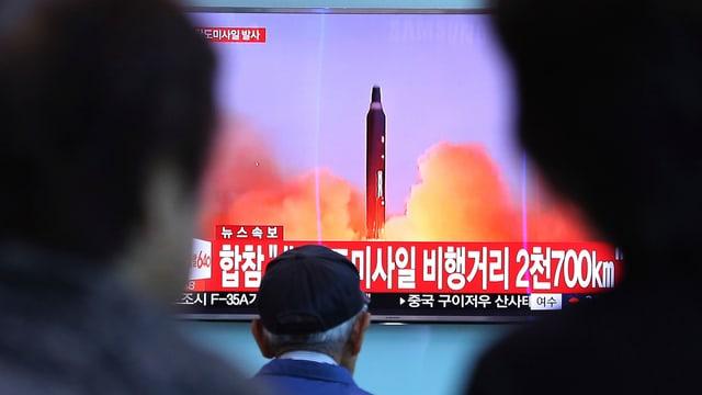 Menschen stehen vor einem Bildschirm, der eine Rakete zeigt.