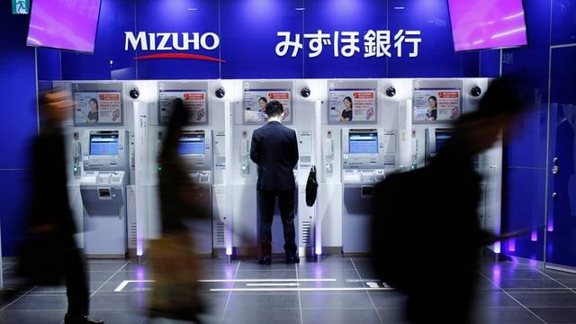 Fünf Geldautomaten einer japanischen Bank, ein Mann bezieht Geld, drei Personen gehen vorbei.