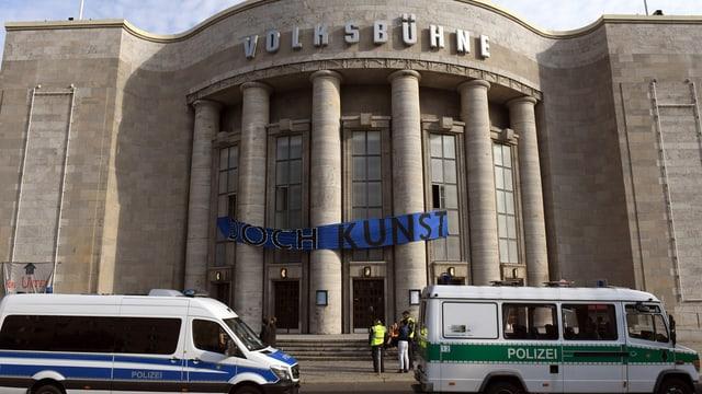Vor der Berliner Volksbühne stehen Polizei-Autos.