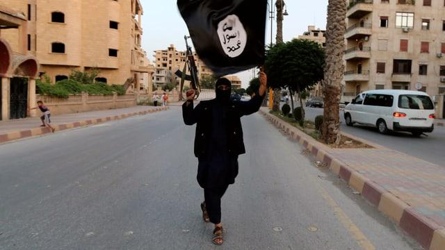 Mann in schwarz mit schwarzer IS-Flagge in einer Strasse, er ist bewaffnet.