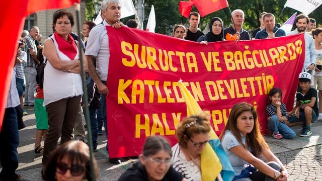 Kurden demonstrieren in Zürich mit Fahnen und Transparenten.