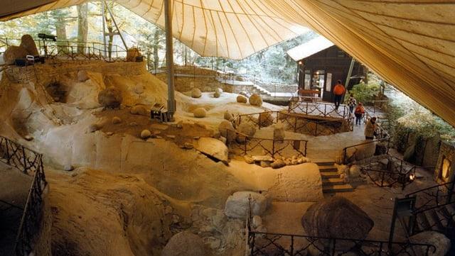 Verschiedene Gletschermühlen mit einem Zelt überdacht.