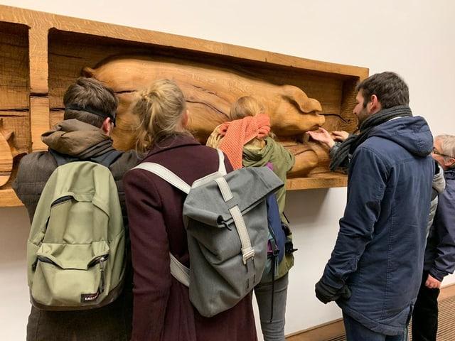 Besucher stehen um ein hölzernes Kunstwerk.