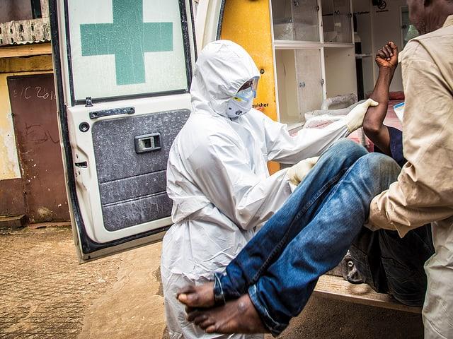 Eine Sanitäterin im Schutzanzug und ein Mann heben einen Patienten mit Ebola-Verdacht in eine Ambulanz in Sierra Leone.