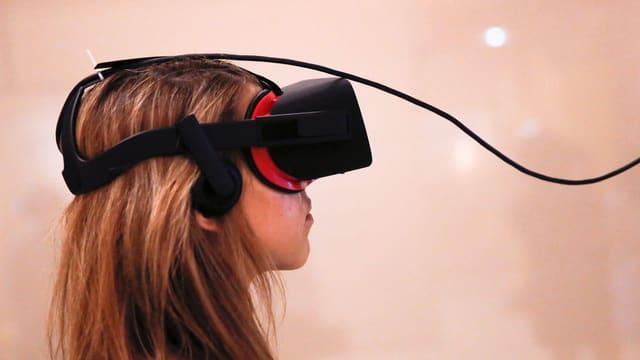 Ein Mädchen trägt eine VR-Brille.