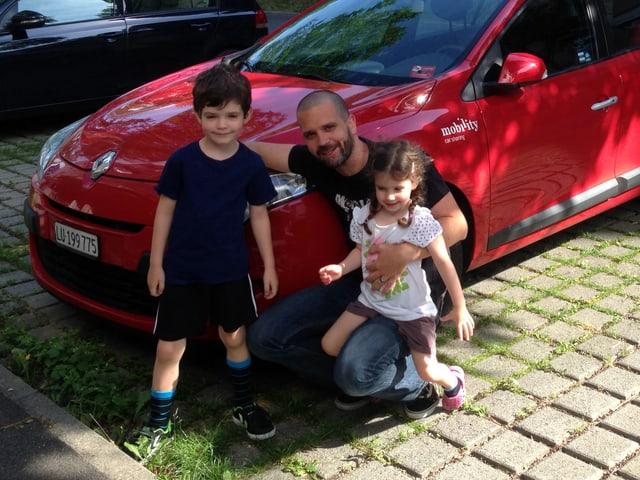 Ein Mann und zwei kleine Kinder vor einem roten Auto.