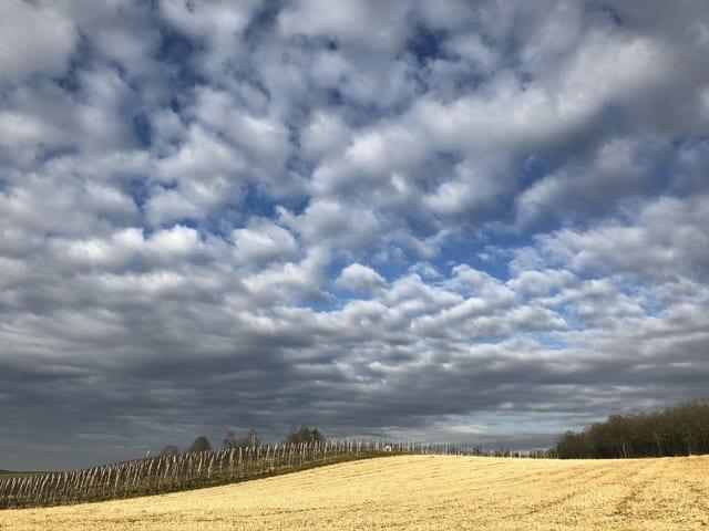 Aufgelockerte Wolken, in der Ferne dichte Wolkenschicht