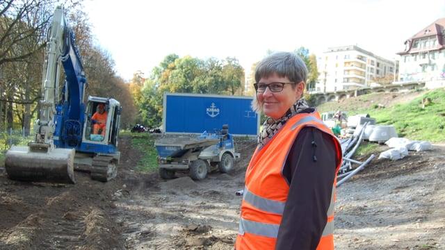 Frau in oranger Warnweste auf einer Baustelle.
