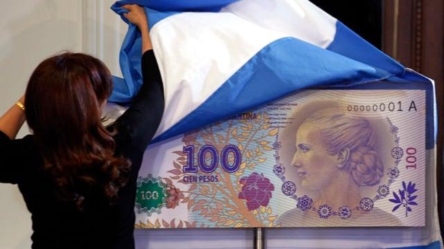 Präsidentin Cristina Fernandez de Kirchner enthüllt eine übergrosse neue 100 Pesos-Note.