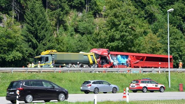 Rotes Auto zwischen Lastwagen.