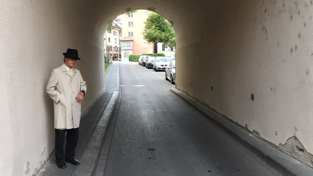 Ein Mann mit Hut steht in einem Tunnel.