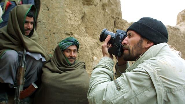 Ein Fotograf macht Nahaufnahmen von bewaffneten Männern.