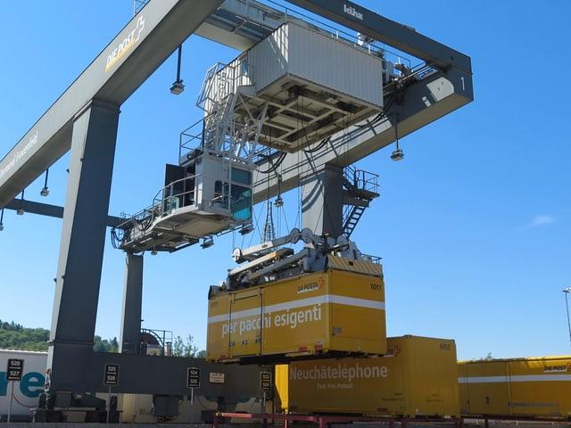 Ein riesiger Hebekran platziert die Container