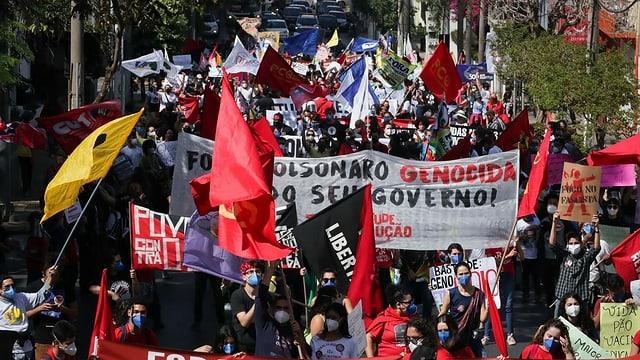 Menschen demonstrieren mit Plakaten.
