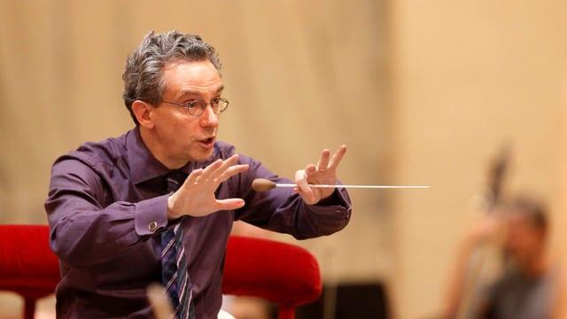 Ein Dirigent mit grauem Haar und Brille.