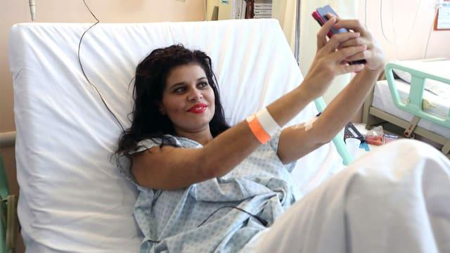 Patientin macht im Krankenhausbett ein Selfie