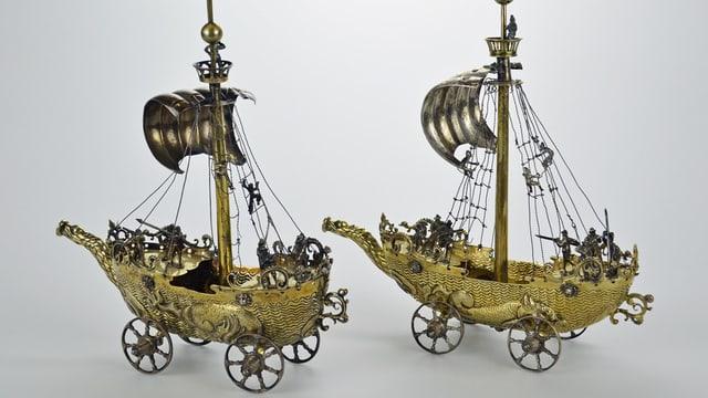 Zwei goldene Segelschiffe mit Rädern.