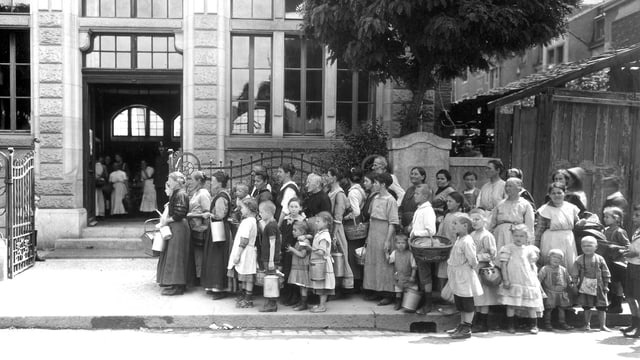 Frauen und Kinder stehen Schlange vor einer Tür. Sie tragen alle Milchkesseli.
