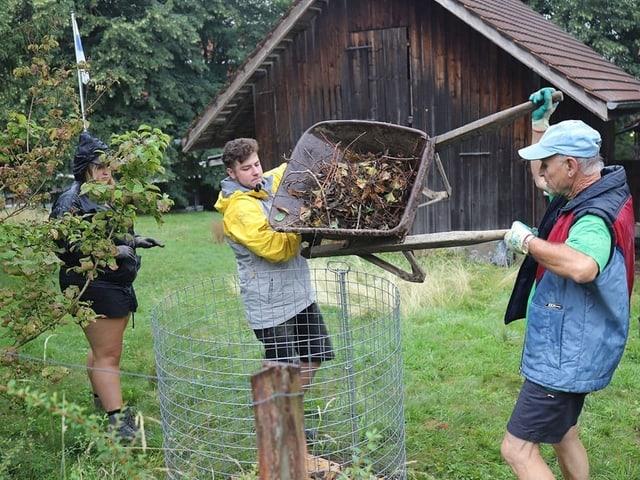 Zwei Männer befüllen einen Kompost mit Ästen und Blättern.