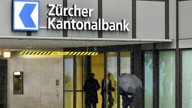 Mann mit Regenschirm vor einer Filiale der Zürcher Kantonalbank