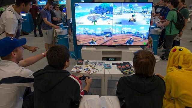 Vier Personen sitzen vor einem Bildschirm und spielen Mario Kart