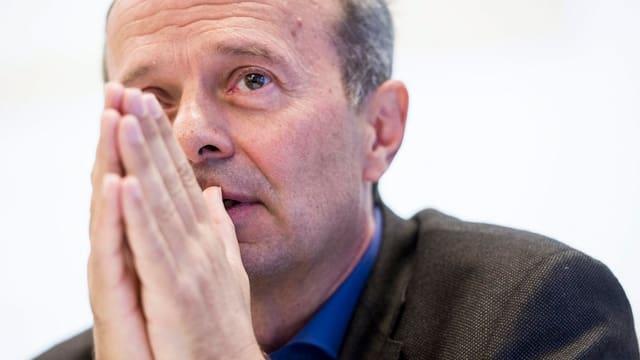 Der Zürcher Polizeivorsteher Richard Wolff bei einer Rede, die Hände hält er zusammen.