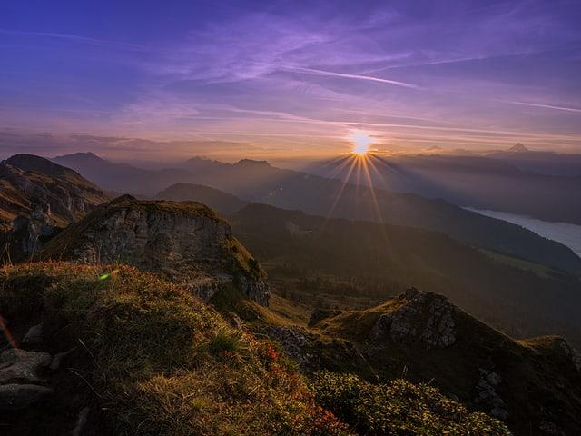 Violetter Himmel mit Bergpanorama, am Horizont geht die Sonne auf.