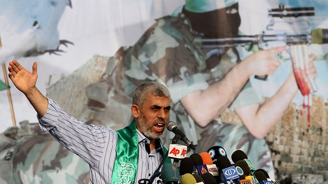 Jahia Sinwar vor einem Bild mit einem Hamas-Kämpfer mit Sturmgewehr.