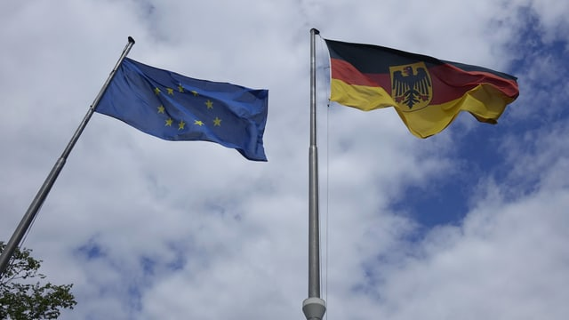 Symbolbild: EU- und deutsche Flagge wehen an je einem Fahnenmast.