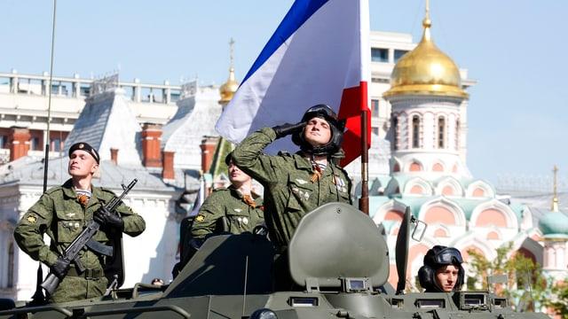 Ein russischer Soldat salutiert an einer Militärparade zum Sieg über Nazideutschland – vor der Krim-Flagge.