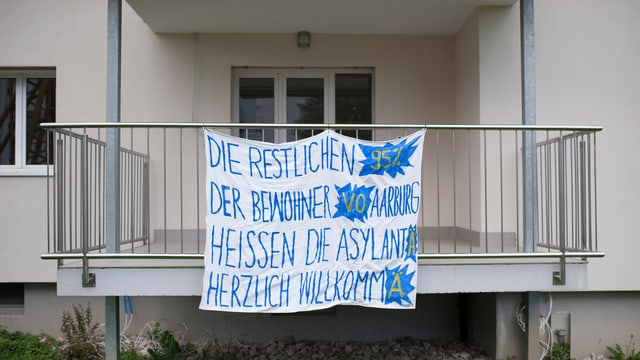 Ein Transparent vor einem Balkon heisst die Asylsuchenden in Aarburg willkommen.