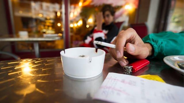 Hand mit Zigarette über einem Aschenbecher. Restauranthintergrund.