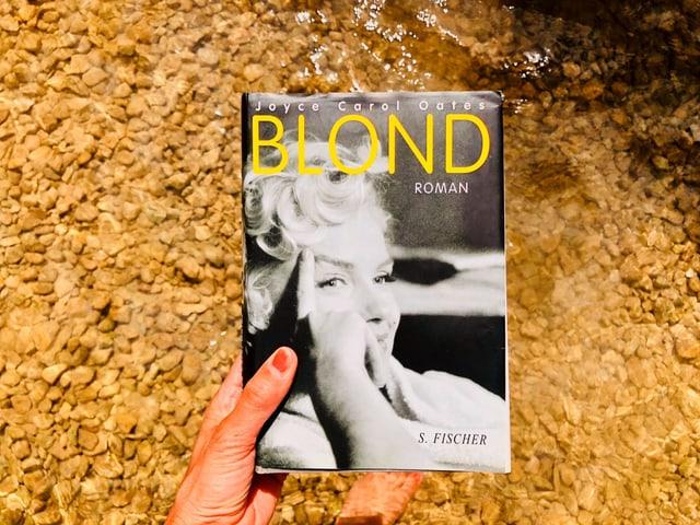 Annette König hält den Roman «Blond» von Joyce Carol Oates vors Wasser