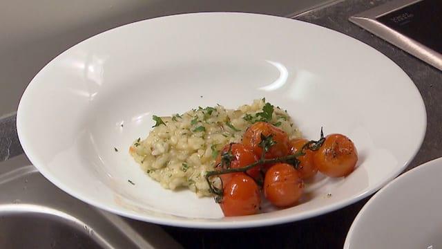 Teller mit Risotto und Tomaten.