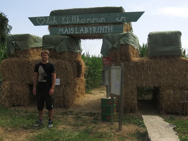 Samuel Mathis steht vor dem Eingang des Maislabyrinths. Auf dem Schild sthet «Herzlich willkommen im Maislabyrinth»