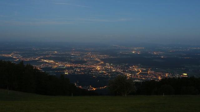 Aussicht vom Berg bei Nacht: Leuchtende Punkte von Häusern und Strassenlampen