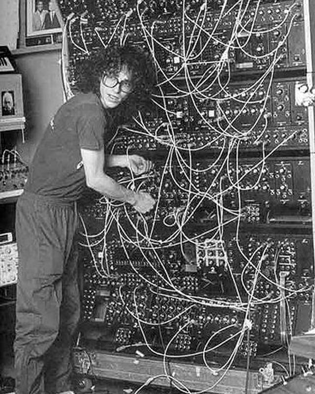 Steve Porcaro von Toto steht vor einem riesigen modularen Synthesizer mit vielen Kabeln und Knöpfen.