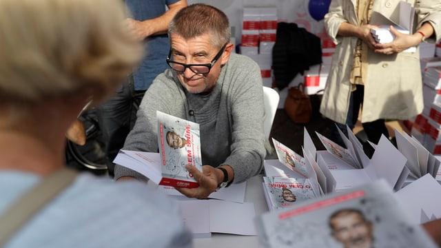 Mann hält Buch in der Hand, vor ihm Menschen