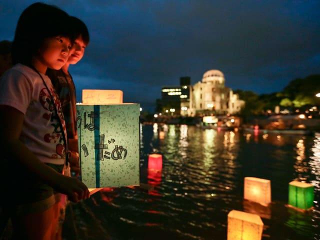 Ein Junge und ein mit setzen auf dem Fluss Papierlaternen aus.