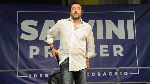 Mann in weissem Hemd vor einem blauen Transparent.