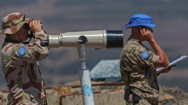 Zwei Blauhelme beobachten das syrische Gebiet.
